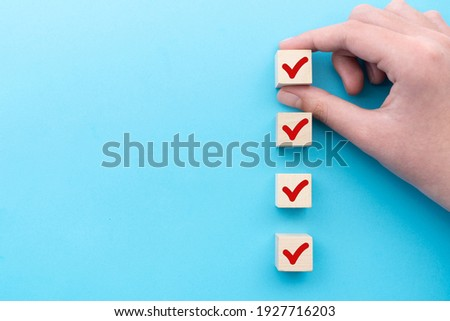 Hand put down the red tick marking wooden cube for checklist or to do list