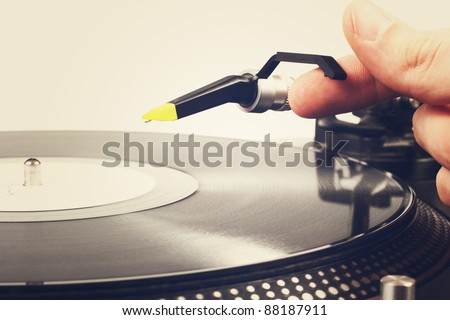 hand put the tonearm on vinyl record