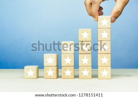 Hand put wooden blocks stacking with the five star symbol on the table, evaluation, Increase rating, Customer experience, satisfaction and best excellent services rating concept. #1278151411