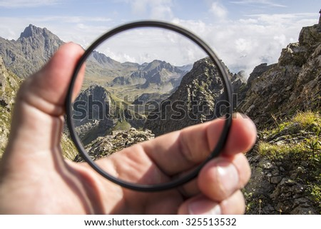 Hand puts a transparent clean protective UV filter to the camera, in the background a beautiful landscape and mountains Foto d'archivio ©