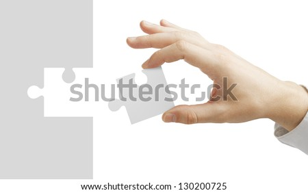 hand puts puzzle isolated on white