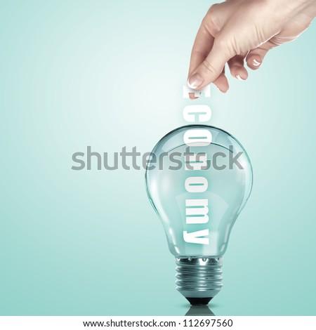 Hand putting a busines term into a light bulb