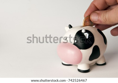 Hand putting a coin into a cow shaped money box