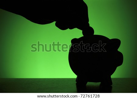 Hand putting a coin into piggy bank against green background