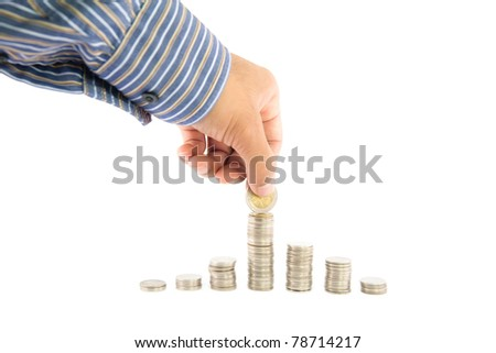 Hand putting a coin on top coins stack, isolate on white