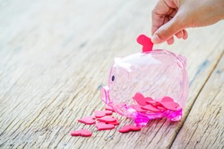 Hand putting a red heart in a piggy bank, Piggy Bank and Red Heart, Concept of love, Charity and Relief Work