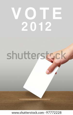 Hand putting a voting ballot in a slot of wooden box on white