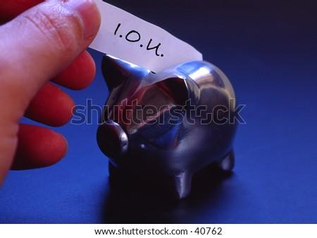 Hand putting an I.O.U. slip into a piggy bank.