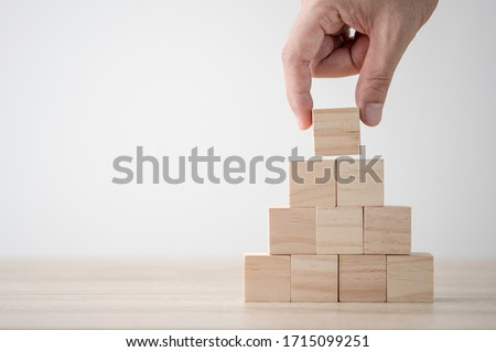 Photo of  Hand putting and stacking blank wooden cubes on table with copy space for input wording and infographic icon.