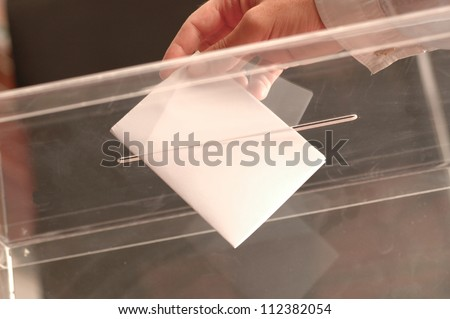 hand putting ballot in the box