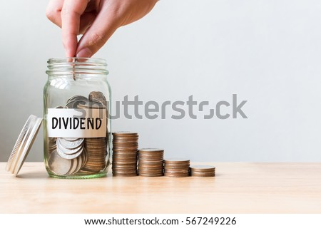 Hand putting coin in jar word dividend with money stack, Concept business finance and investment