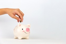 Hand putting coin in piggy bank on white background, Saving concepts