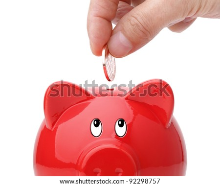 Hand putting coin into a piggy bank