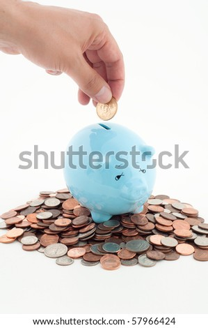 Hand Putting Coin into Piggy Bank that is Already Full