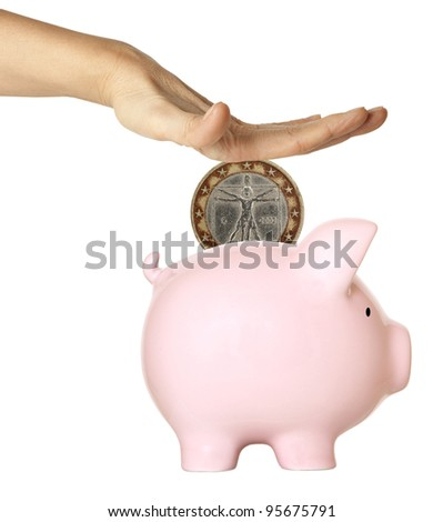 Hand putting coin into the pink piggy bank