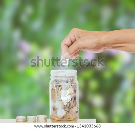 Hand putting Coins in glass jar.Compose classic and vintage tones.