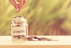 Hand putting Coins in glass jar with DONATE word written text label for giving and donation concept