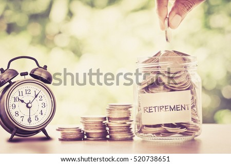 Hand putting Coins in glass jar with retro alarm clock  for time to money saving for retirement concept , vintage retro color tone