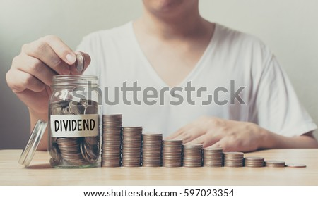 Hand putting coins in jar word dividend with money stack step growing growth saving money, Concept finance business investment