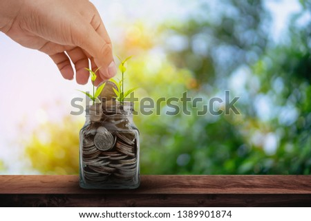 Hand putting coins into clear bottle on wood table with green bokeh natural background. #1389901874