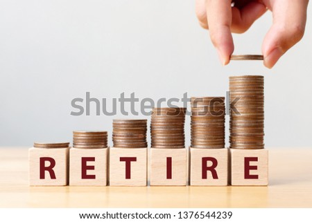 Hand putting coins on stack stair as step growing growth and wooden cube block with word RETIRE. Money pension retirement concept