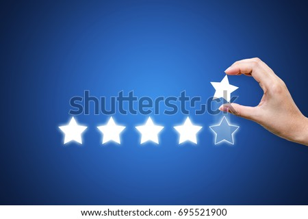 Hand putting five star symbol to increase rating of company with dark blue background, Copy space for text or headline #695521900