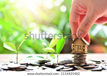 hand putting house model on coins saving for concept investment fund mortgage finance and home loan