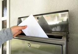 hand putting mail in mailbox