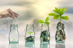 Hand putting mix coins and seed in clear bottle on cityscape photo blurred cityscape background,Business investment growth concept