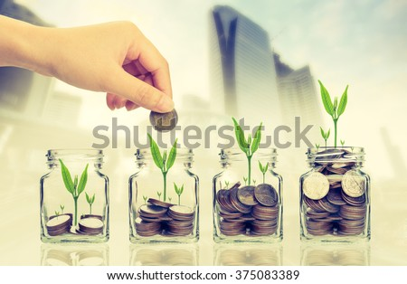 Hand putting money coins and seed in clear bottle on cityscape photo blurred cityscape background,Business investment growth concept