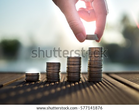 Hand putting money coins stack growing, saving money for purpose concept