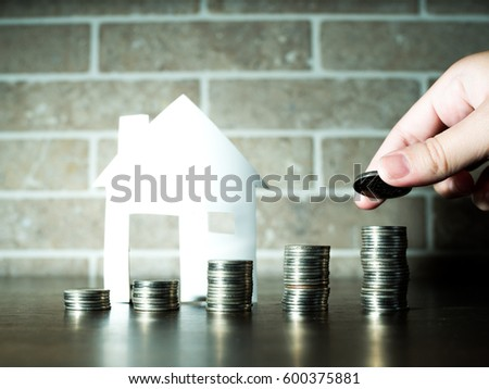 Hand putting money coins stack growing with house behind, saving money for home concept #600375881
