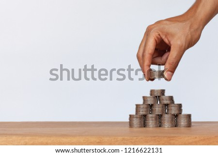 Hand putting money coins to row of coins on wooden table. Concept for property, ladder ,real estate investment and saving #1216622131