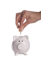 Hand putting money in a piggy bank, white background.