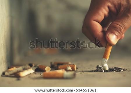 Hand putting out a cigarette,cigarette butt on Concrete floor, bare cement.