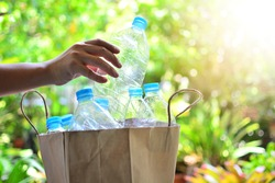 hand putting plastic bottle in paper bag for recycling