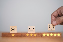 Hand putting smiley face and golden yellow stars which print screen on wooden cube block for customer survey quality of product and service , Customer evaluation scorecard concept.