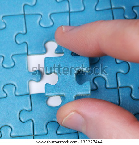 Hand putting the last piece of puzzle in a gap