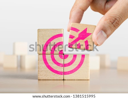 Hand putting the last piece of wooden blocks with the dart target icon. Goal, business goal, achieving a goal or success concept. #1381515995