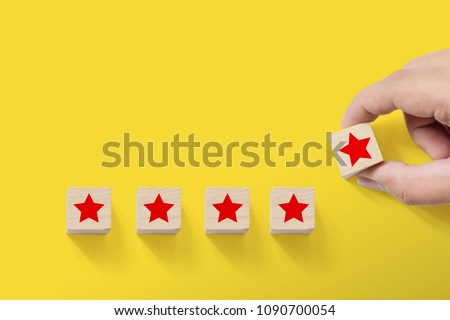 Hand putting wood block with five star symbol to increase rating of company with yellow background, Copy space for text or headline #1090700054