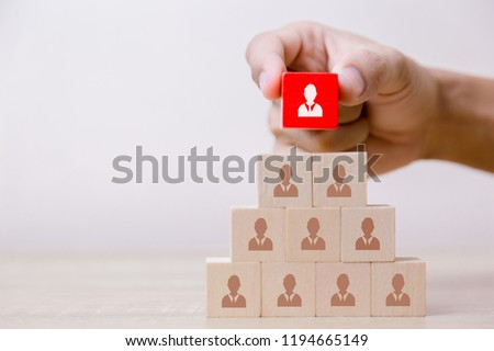 Hand putting wood cube block on top pyramid,human resource management and recruitment business concept, Business Strategy to success.