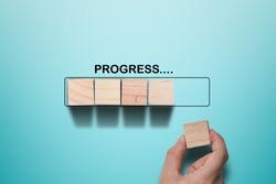 Hand putting wooden cube on virtual infographic rectangle block with progress wording. Job progressive concept.