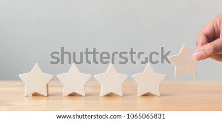 Hand putting wooden five star shape on table. The best excellent business services rating customer experience concept #1065065831