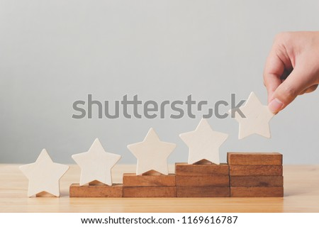 Hand putting wooden five star shape on table. The best excellent business services rating customer experience concept #1169616787