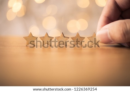 Hand putting wooden five star shape on table. The best excellent business services rating customer experience concept. #1226369254