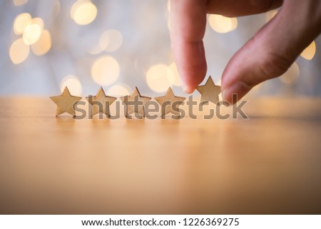 Hand putting wooden five star shape on table. The best excellent business services rating customer experience concept. #1226369275