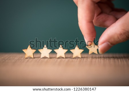 Hand putting wooden five star shape on table. The best excellent business services rating customer experience concept. #1226380147