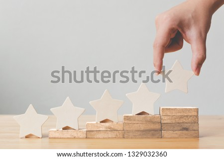 Hand putting wooden five star shape on table. The best excellent business services rating customer experience concept #1329032360