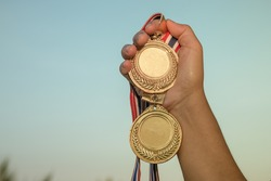 hand raised and holding gold two medals against sky. award concept