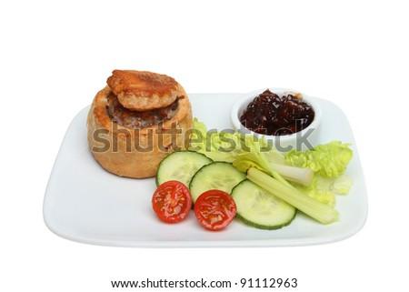 Hand raised pork pie with pickle and salad garnish on a plate isolated against white